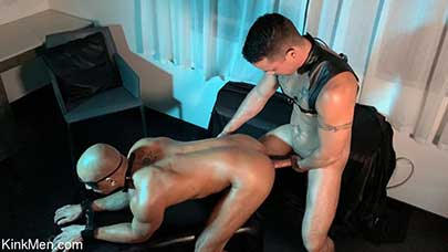Nic Sahara has Zario Travezz naked and blindfolded on his back with his wrists and ankles cuffed together. Nic sits in the corner in a leather harness, rubbing his hard cock through his leather jock.